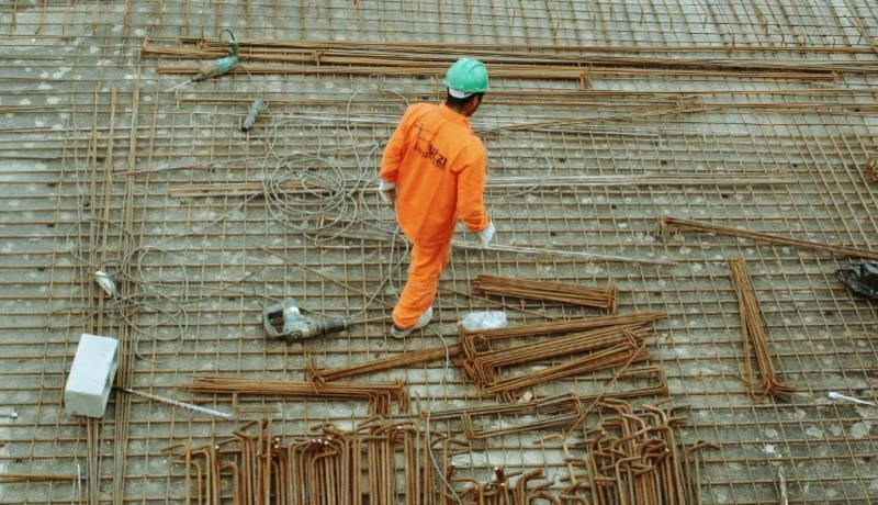A construction worker in orange uniform walking on the construction site.